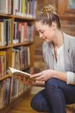 Blonder Lehrer, der Buch in der Bibliothek sucht Lizenzfreie Stockfotografie