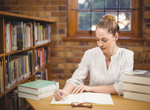 Blonder Lehrer, der in der Bibliothek korrigiert Stockfotos