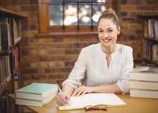 Blonder Lehrer, der in der Bibliothek korrigiert Stockfoto