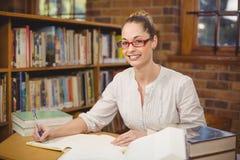Blonder Lehrer, der in der Bibliothek korrigiert Lizenzfreies Stockbild