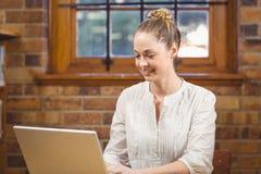 Blonder Lehrer, der Laptop in der Bibliothek verwendet Lizenzfreies Stockfoto