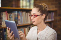 Blonder Lehrer, der Tablette in der Bibliothek verwendet Stockbilder