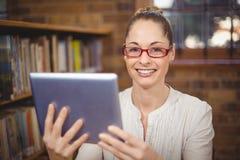 Blonder Lehrer, der Tablette in der Bibliothek verwendet Stockfotografie