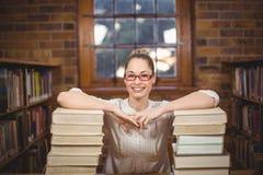 Blonder Lehrer, der zwischen Büchern in der Bibliothek steht Lizenzfreie Stockfotografie