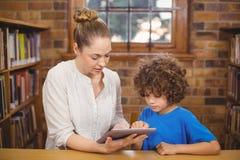 Blonder Lehrer und Schüler, der Tablette in der Bibliothek verwendet Stockbilder