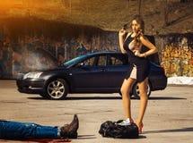 Blonder Luxusfrauenstand über Tasche voll dampfenden Autos Geld Amin Stockfotos