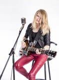 Blonder Mädchengitarrist mit E-Gitarre lernt Spiellied, sitzt auf Stuhl, singt in Retro- Mikrofon Lehrerin Stockfotografie