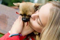 Blonder Mädchenholding-Haustierhund Stockfoto