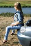 Blonder Mädchenmechaniker, der auf dem Auto sitzt Lizenzfreies Stockfoto
