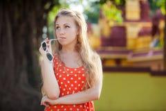 Blonder Mädchenstand und -haltungen in der Orange mit weißem Tupfen kleiden an Stockfotografie