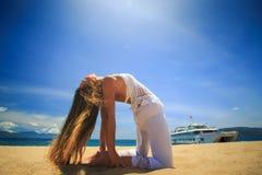 blonder Mädchenstand in Yoga asana biegen Kamel auf Strand zurück Lizenzfreie Stockfotos