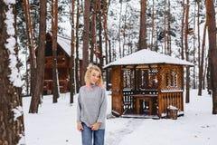 Blonder Mädchenweg nahe einem Gazebo im Winterwald Stockbild