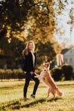 Blonder Mädchenzug ihr Hund border collie im grünen Park im Sonnenschein lizenzfreies stockfoto
