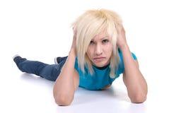 Blonder männlicher Jugendlicher, der auf Fußboden liegt Lizenzfreies Stockfoto