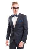 Blonder männlicher vorbildlicher tragender Anzug, bowtie und Sonnenbrille Stockfotos