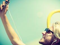 Blonder Mann äußeres nehmendes selfie mit Smartphone Stockbild