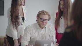 Blonder Mann in den Gläsern, die in einem hellen bequemen Büro mit netbook am Tisch sitzen Zwei Mädchen in der Stellung der forme stock video footage