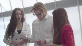 Blonder Mann in den Gläsern seine Idee zwei weiblichen Kollegen erklärend, die auf beiden Seiten von ihm in einem hellen bequemen stock video