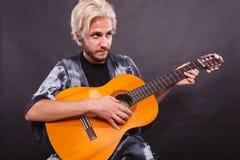 Blonder Mann, der Akustikgitarre spielt Lizenzfreie Stockbilder