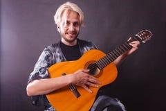 Blonder Mann, der Akustikgitarre spielt Stockfotografie