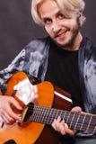 Blonder Mann, der Akustikgitarre spielt Lizenzfreie Stockfotos