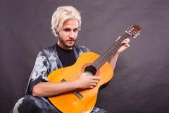 Blonder Mann, der Akustikgitarre spielt Stockfoto
