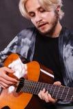 Blonder Mann, der Akustikgitarre spielt Stockfotos