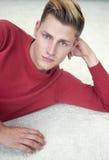 Blonder Mann, der auf Boden liegt und Kamera betrachtet Stockbild