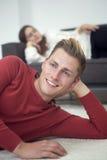 Blonder Mann, der auf dem Teppich und Frau schlafen auf Couch liegt Stockbilder