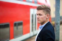 Blonder Mann, der auf den Zug wartet Lizenzfreie Stockfotografie