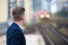 Blonder Mann, der auf den Zug wartet Lizenzfreies Stockbild