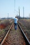 Blonder Mann, der auf die Schienen geht Lizenzfreie Stockfotografie