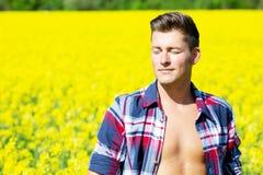 Blonder Mann, der auf einem gelben Gebiet steht und die Sonne genießt Stockbilder