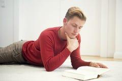 Blonder Mann, der auf Teppich liegt und ein Buch liest Stockfoto