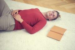 Blonder Mann, der auf Teppich mit einem Buch liegt Stockfoto