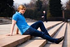 Blonder Mann, der draußen sitzt Stockfoto