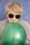 Blonder Mann, der einen grünen Ballon durchbrennt Lizenzfreie Stockbilder