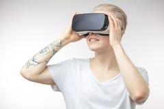 Blonder Mann, der Erfahrung unter Verwendung der VR-Kopfhörergläser virtueller Realität erhält Lizenzfreie Stockbilder
