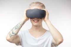 Blonder Mann, der Erfahrung unter Verwendung der VR-Kopfhörergläser virtueller Realität erhält Stockfoto