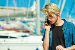 Blonder Mann, der am Handy spricht Stockfotografie