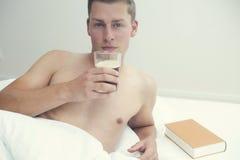 Blonder Mann, der im Bett mit Kaffee und einem Buch liegt Stockfoto
