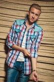 Blonder Mann, der im Studio beim Reparieren seines Hemdes aufwirft Lizenzfreie Stockbilder