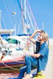 Blonder Mann, der nahe Hafen im Sommer sitzt Stockfoto