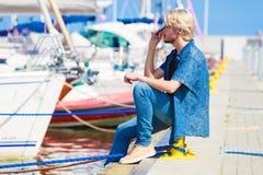 Blonder Mann, der nahe Hafen im Sommer sitzt Stockfotos