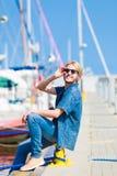 Blonder Mann, der nahe Hafen im Sommer sitzt Stockfotografie