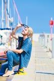 Blonder Mann, der nahe Hafen im Sommer sitzt Lizenzfreies Stockbild