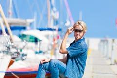 Blonder Mann, der nahe Hafen im Sommer sitzt Lizenzfreie Stockfotografie