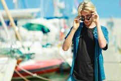 Blonder Mann, der nahen Hafen im Sommer steht Stockfoto