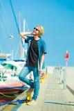 Blonder Mann, der nahen Hafen im Sommer steht Lizenzfreie Stockfotografie