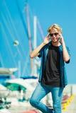 Blonder Mann, der nahen Hafen im Sommer steht Lizenzfreie Stockfotos
